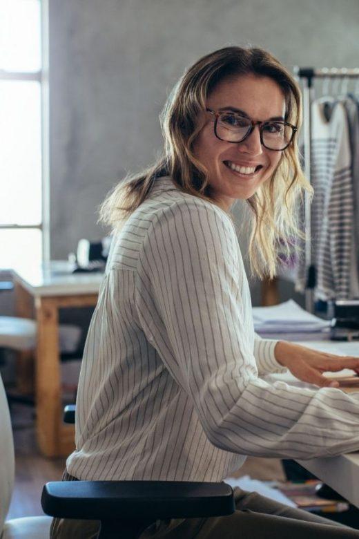 Recupero carrelli abbandonati, donna sorridente mentre lavora alla scrivania davanti al computer