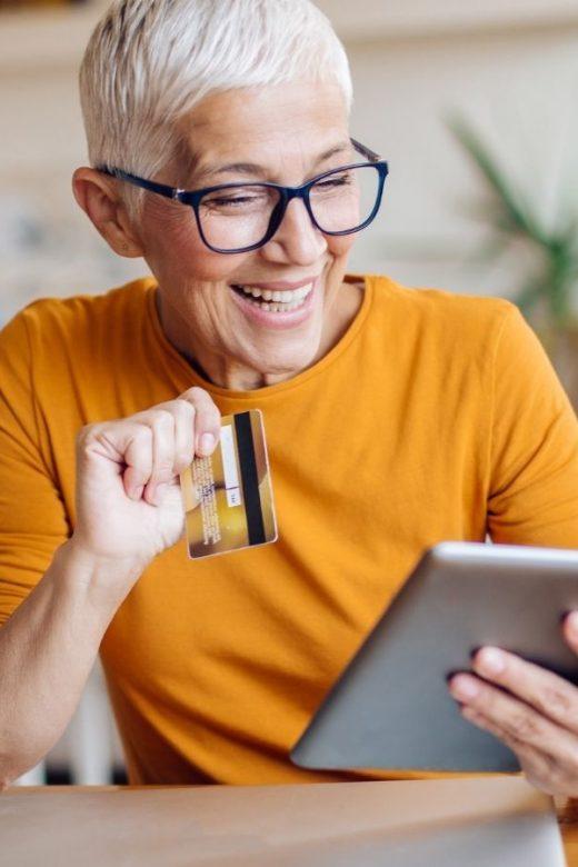 Relazioni con i clienti: donna sorride sorridente davanti al tablet mentre fa un acquisto online