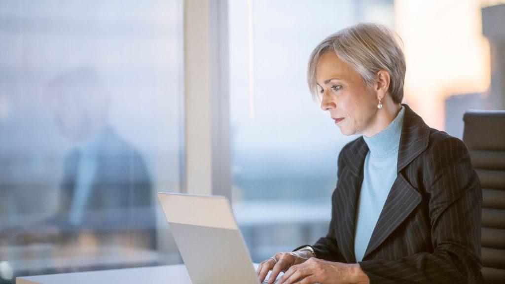 email di benvenuto: donna al computer prepara le mail da inviare