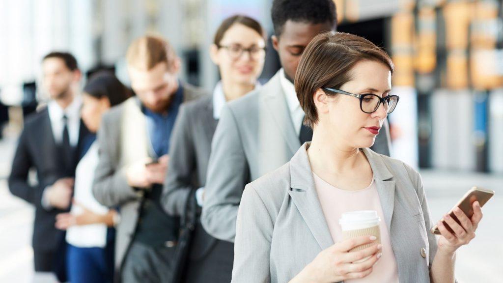 messaggi push: persone in fila guardano le notifiche sullo smartphone