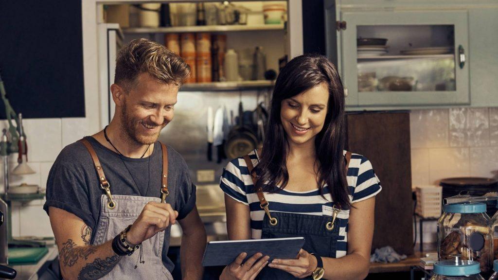 differenza tra uppsell e cross sell: uomo e donna felici fanno acquisti online