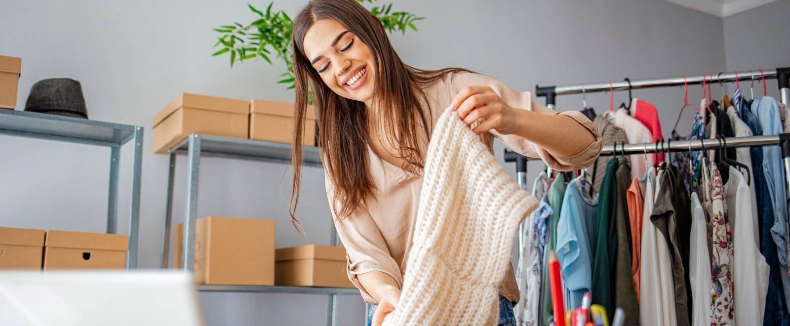 Vendere on-line: donna felice prepara la spedizione dei prodotti
