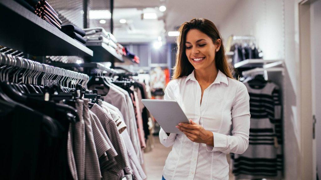 vendere on-line: valuta la fase di fullfillment dell'ordine. Donna sorridente controlla ordini online