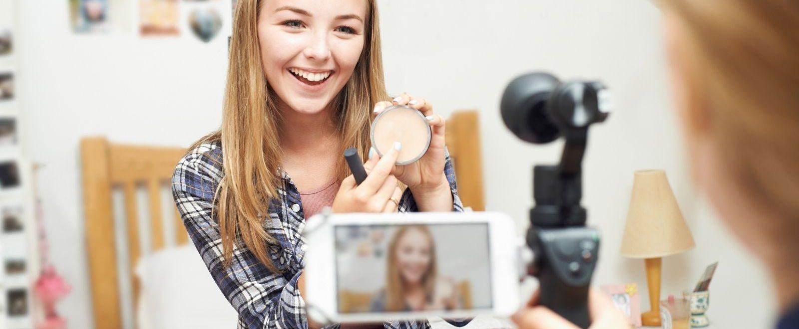 Video content marketing: ragazza sorridente mostra il prodotto alla videocamera