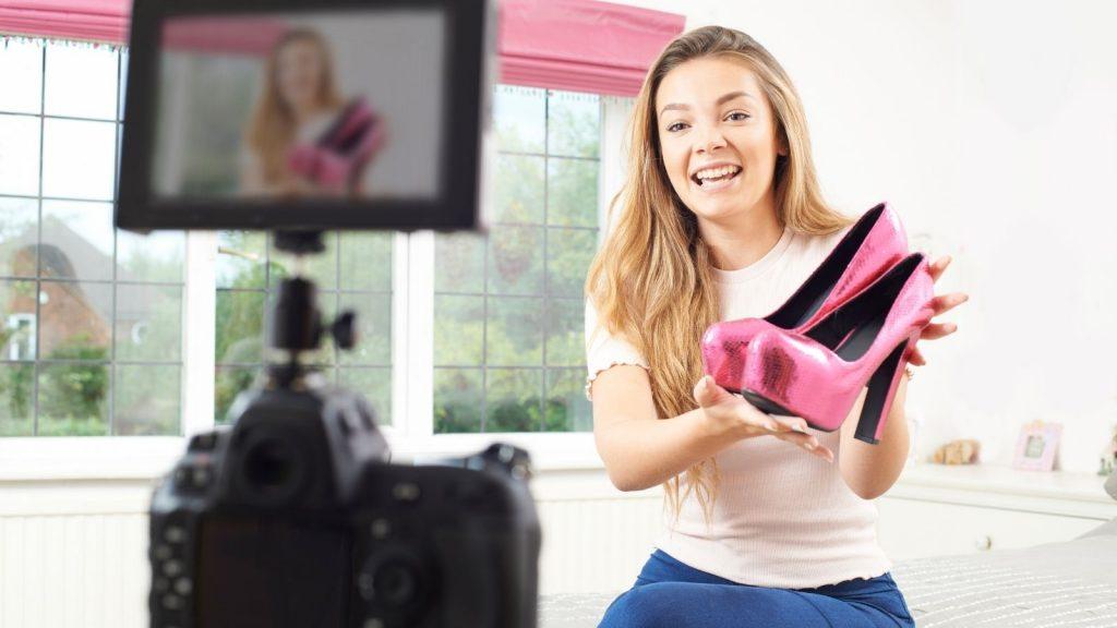 Video content marketing: donna sorridente mostra un paio di scarpe