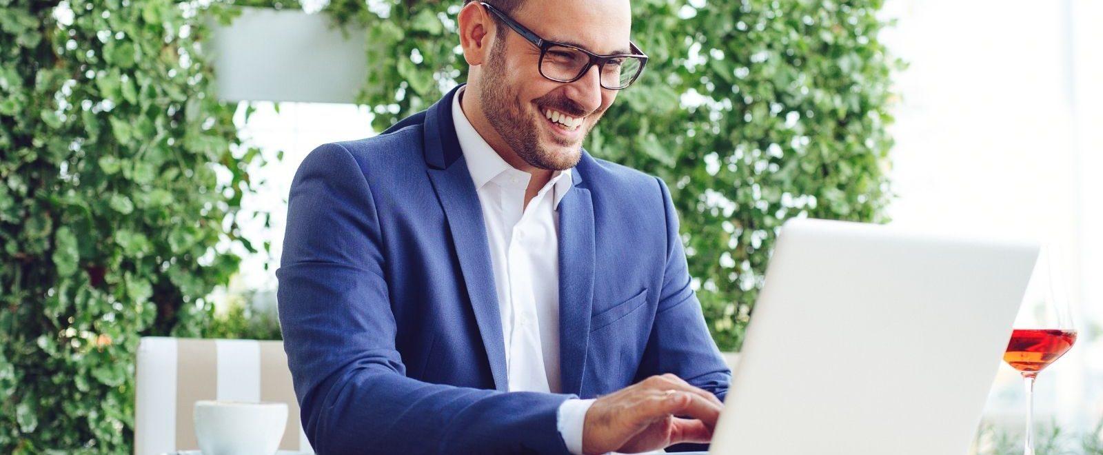 Welcome email: uomo d'affari sorride soddisfatto mentre invia la sequenza email di benvenuto