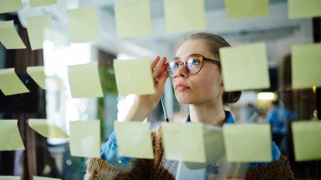 Obiettivi da raggiungere: donna guarda bacheca con post-it