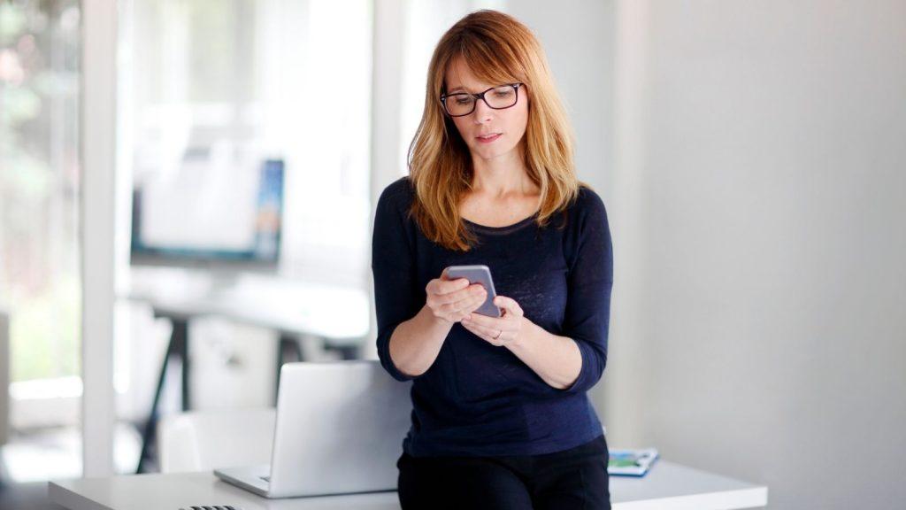 Aumentare gli iscritti alla newsletter: donna controlla la posta elettronica sullo smartphone