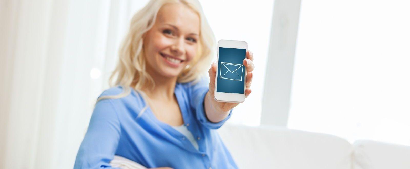 Come aumentare iscrizioni alla newsletter: donna sorridente riceve email