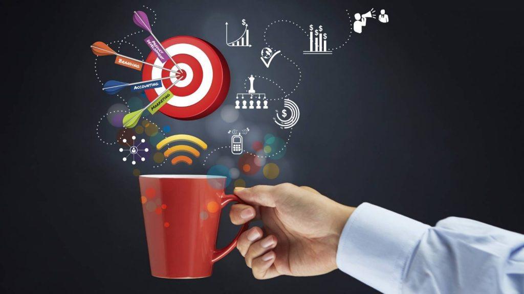 Raggiungere gli obiettivi: nell'immagine una mano tiene una tazza da cui emergono simboli di pianificazione e business