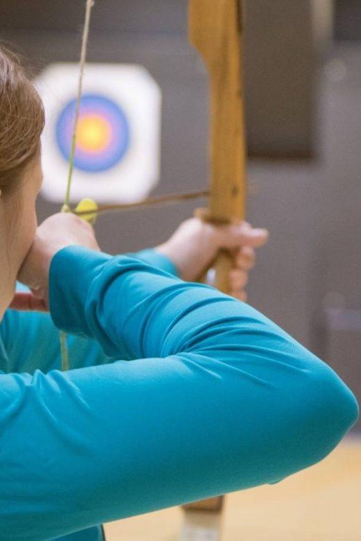Raggiungere obiettivi: donna tira freccia con l'arco