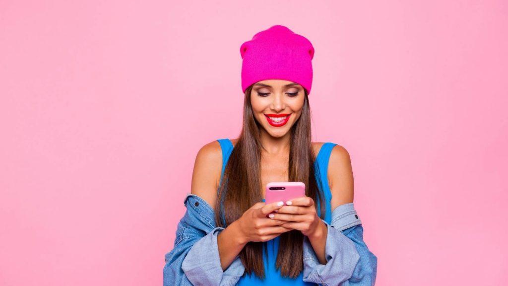 I blog ti permettono di incontrare le tue buyer personas: donna sorridente legge il blog dallo smartphone.